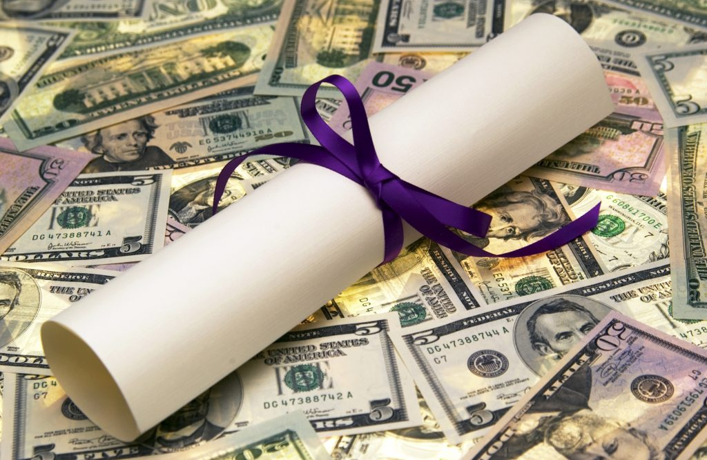 pile of money with rolled up diploma tied with a blue ribbon
